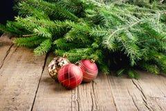 O cartão para os feriados do Natal enfeita o fundo de madeira do Natal do fundo dos brinquedos do Natal dos ramos Fotografia de Stock