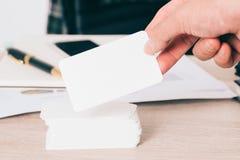 O cartão vazio à disposição no fundo borrado da mesa de escritório usa-nos para o molde ascendente do projeto da informação da id Fotografia de Stock