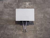 O cartão vazio guardou por um grampo da pasta em uma superfície de madeira fotografia de stock
