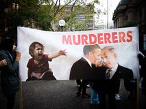 O cartaz grande da mostra do protestador diz o ` dos assassinos do ` com imagem do presidente Obama e dos presidentes de Israel Foto de Stock
