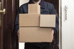 O carteiro traz com pacotes fotografia de stock