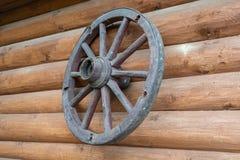 O cartwheel velho pendura na parede de uma casa de log imagens de stock
