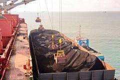 O carvão da carga das barcas da carga em um portador de maioria que usa o navio cranes e garras no porto de Samarinda, Indonésia foto de stock royalty free