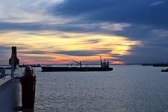 O carvão da carga das barcas da carga em um portador de maioria que usa o navio cranes e garras no porto de Samarinda, Indonésia fotos de stock