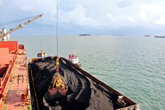 O carvão da carga das barcas da carga em um portador de maioria que usa o navio cranes e garras no porto de Samarinda, Indonésia fotografia de stock