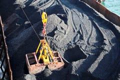 O carvão da carga das barcas da carga em um portador de maioria que usa o navio cranes e garras no porto de Samarinda, Indonésia imagem de stock