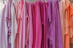 O casaco de pele e as calças pesam em ganchos na loja Fotografia de Stock