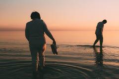 O casal adulto mantém sapatas disponivéis e anda na água Fotografia de Stock Royalty Free