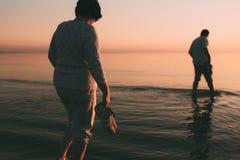 O casal adulto mantém sapatas disponivéis e anda na água Imagens de Stock