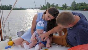 O casal agradável com criança relaxa no iate, no marido e no associado com o infante que descansa no barco de prazer, filme