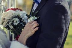 O casal, as mãos e os dedos com anéis, flores Foto de Stock Royalty Free