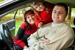 O casal e a menina sentam-se no carro no parque Fotografia de Stock