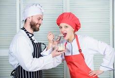 O casal feliz tem a alegria junto na cozinha Ingrediente secreto pela receita Uniforme do cozinheiro Planeamento do menu culinary fotografia de stock royalty free