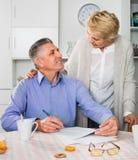 O casal maduro discute o contrato e o sinal docum importante imagens de stock royalty free