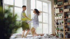 O casal novo é de salto e dançando na cama de casal na sala clara com grandes janelas, os povos felizes estão tendo o divertiment video estoque