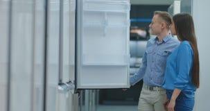 O casal novo aberto a porta do refrigerador inspeciona o projeto e a qualidade antes de comprar em uns produtos eletrónicos de c video estoque