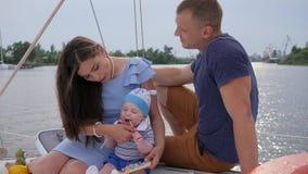 O casal novo com o filho que descansa no iate, no marido e no associado com infante relaxa no barco de prazer, vídeos de arquivo