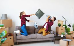 O casal novo feliz transporta-se ao apartamento novo e rindo, o salto, luta descansa imagens de stock