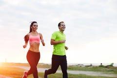 O casal novo que corre avante no lado de mar Imagens de Stock Royalty Free