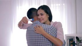 O casal saudável encontrado sobre a gravidez e abraça-se com felicidade na sala brilhante video estoque
