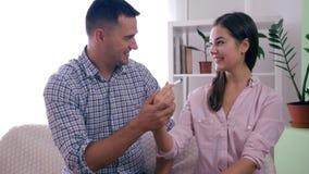 O casal saudável feliz com teste de gravidez aprendeu sobre o bebê futuro e alegremente o abraço na sala em casa video estoque