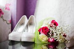 O casamento calça o branco na tabela e em um ramalhete Foto de Stock Royalty Free
