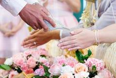 O casamento tailandês, fecha-se acima das mãos que derramam a água nas mãos fotografia de stock royalty free