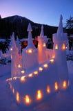 O castelo da neve iluminou-se por velas e por crepúsculo Imagem de Stock Royalty Free