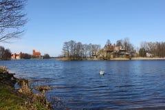 O castelo de Trakai e a casa velha no lago suportam Imagens de Stock Royalty Free