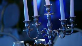 O castiçal com velas queima-se no restaurante escuro, velas nos castiçal, velas decorativas que queimam-se, decoração da cera video estoque