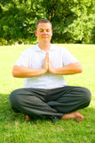 O Caucasian novo Meditate no parque fotografia de stock