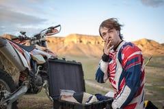 O cavaleiro da bicicleta relaxa montanhas perto da motocicleta, fumo da antena imagens de stock royalty free