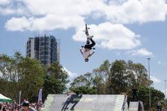 O cavaleiro de BMX que executam truques e os saltos sobre uma rampa em Sydney Park dão um ciclo o centro imagem de stock
