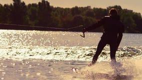 O cavaleiro de Wakeboard que move-se rapidamente em espirra da água no por do sol dourado vídeos de arquivo
