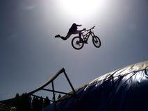 O cavaleiro do bmx de Dirtbike salta contra o sol Foto de Stock Royalty Free