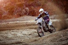 O cavaleiro do motocross cria uma grande nuvem da poeira e dos restos Foto de Stock Royalty Free