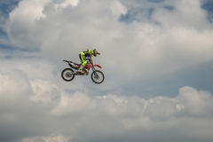 O cavaleiro do motocross do estilo livre realiza um truque com a motocicleta no fundo do céu azul da nuvem Voo no céu em um moto Fotos de Stock Royalty Free