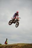 O cavaleiro do motocross no vôo remove a película protetora fotografia de stock royalty free