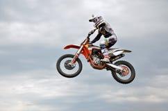 O cavaleiro do motocross salta altamente de encontro ao céu Fotografia de Stock Royalty Free