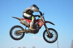 O cavaleiro do motocross salta, céu azul imagem de stock royalty free