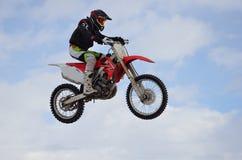 O cavaleiro do motocross salta, céu azul fotografia de stock