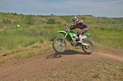 O cavaleiro do MX na bicicleta salta de um monte Imagens de Stock Royalty Free