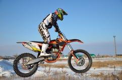 O cavaleiro na bicicleta para o motocross voa sobre o monte fotografia de stock
