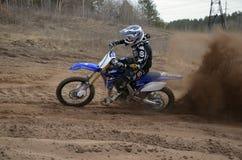 O cavaleiro na motocicleta acelerou ao longo de um arenoso a trilha Imagens de Stock