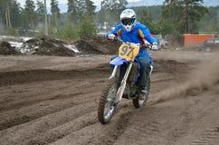 O cavaleiro na motocicleta acelerou ao longo de um arenoso a trilha Imagem de Stock
