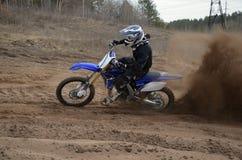 O cavaleiro na motocicleta acelerou ao longo de um arenoso a trilha Fotografia de Stock Royalty Free