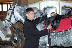 O cavaleiro novo aperta um selar-girth Imagens de Stock