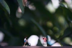 O cavaleiro pequeno do fotógrafo e da bicicleta modela figuras no assoalho de madeira com fundo da natureza do verde do borrão Fotos de Stock Royalty Free