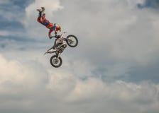 O cavaleiro profissional do motocross do estilo livre realiza um truque com a motocicleta no fundo do céu azul da nuvem Alemão-St Imagens de Stock