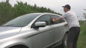 O cavalheiro no t-shirt branco lava ativamente o carro cinzento moderno video estoque